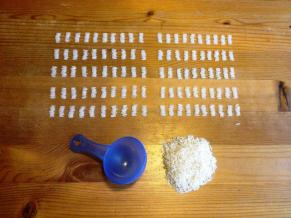 50 ml Reis. Davon 1000 Reiskörner in 100 Zehnerreihen angetreten, darunter der Messlöffel und der restliche Reis.