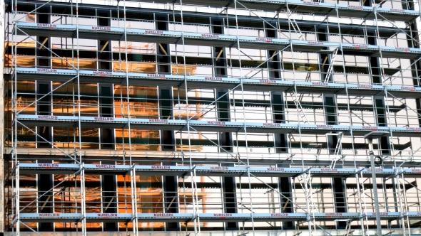 Fensterfront eines Neubaus hinter Baugerüst
