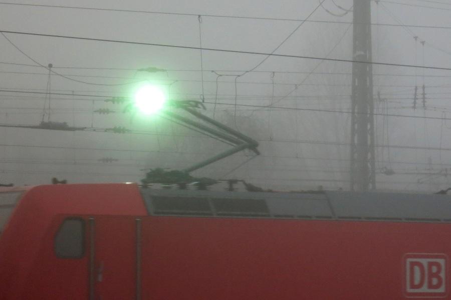 Funkenüberschlag zwischen der Oberleitung und dem Bügel einer Elektrolok an einem düster-nebligen Morgen im Bahnhof