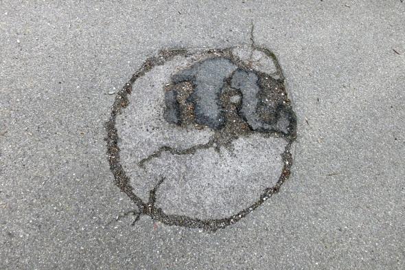Asphaltierter Radweg mit ungefähr kuchentellergroßer runder Flickstelle, in der mehrere Risse und ein weiterer, dunklerer Asphaltflicken insgesamt wie ein maskierter Smiley aussehen.